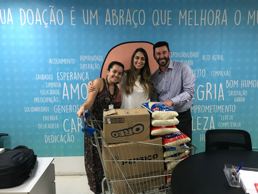 As analistas de RH da Companhia de Estágios Bruna Romano (esq.) e Raquel Oliveira (dir.) entregam doação a Vagner Carvalho (centro), superintendente da Fundação Criança, instituição mantenedora do ITACI/Arquivo Pessoal